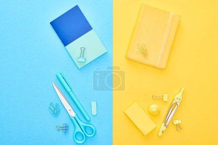 Photo pour Vue supérieure des bloc-notes jaunes et bleus avec la papeterie différente sur le fond bicolor - image libre de droit