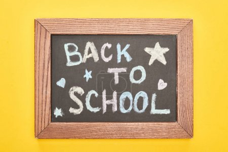 Photo for Chalkboard in wooden frame with back to school inscription with small stars and hearts on yellow background - Royalty Free Image
