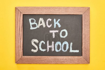Photo for Chalkboard in wooden frame with back to school inscription on yellow background - Royalty Free Image