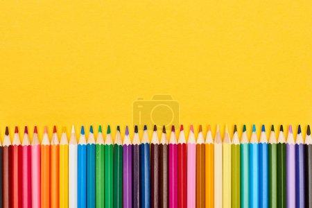 Photo pour Crayons aiguisés de couleur vive isolés sur du jaune - image libre de droit