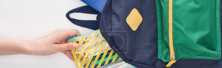 Photo for Schoolgirl taking yellow pencil case from blue schoolbag isolated on white - Royalty Free Image