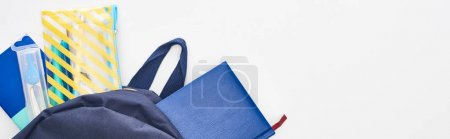 Photo for Panoramic shot of blue schoolbag with notepads, pencil case and school supplies isolated on white - Royalty Free Image