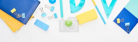 Photo for Panoramic shot of blue and yellow scattered school supplies with notepads and pencil case isolated on white - Royalty Free Image