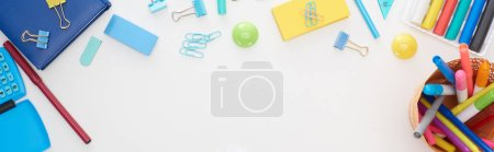 Photo for Panoramic shot of blue and yellow scattered school supplies and cup with colorful felt-tip pens isolated on white - Royalty Free Image