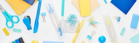 Photo for Panoramic shot of blue and yellow scattered school supplies with notepads isolated on white - Royalty Free Image