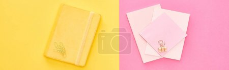 Photo pour Panoramic shot of yellow notepad and pink sheets of paper on bicolor background - image libre de droit