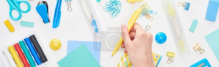 Photo pour Panoramic shot of schoolgirl hand with yellow pen near stationery isolated on white - image libre de droit
