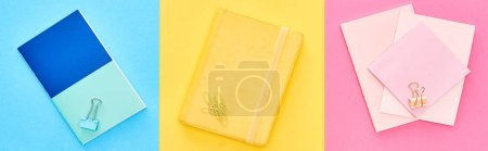 Photo for Panoramic shot of yellow and blue notepads near pink sheets of paper on tricolor background - Royalty Free Image