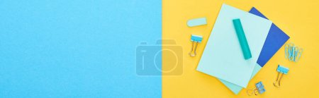 Photo for Panoramic shot of different blue stationery with sheets of paper on bicolor background - Royalty Free Image