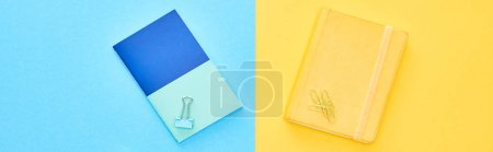 Photo for Panoramic shot of blue and yellow notepads on bicolor background - Royalty Free Image