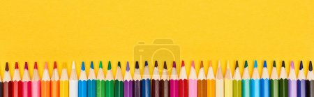 Photo for Panoramic shot of straight line of color pencils isolated on yellow - Royalty Free Image