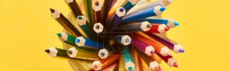Foto de Toma panorámica de lápices de colores afilados y brillantes aislados en amarillo - Imagen libre de derechos