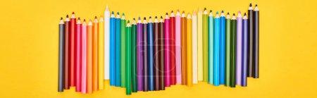 Photo pour Panoramic shot of color pencils set isolated on yellow - image libre de droit