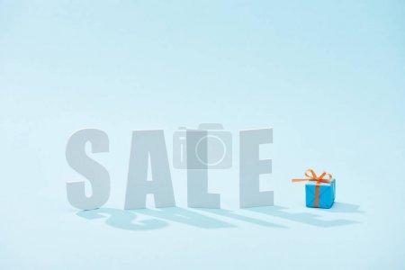 Photo pour Blanc vente lettrage et boîte cadeau festive sur fond bleu - image libre de droit