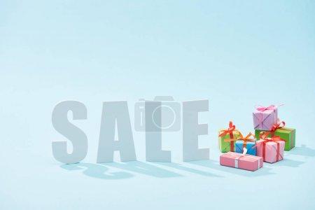 Photo pour Blanc vente lettrage et boîtes cadeaux festives sur fond bleu - image libre de droit