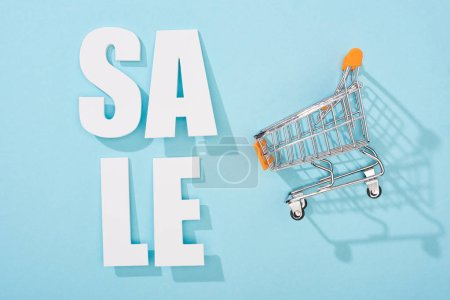 top view of white sale lettering and decorative shopping cart on blue background