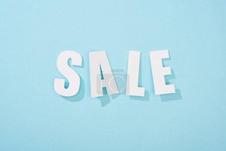Photo pour Vue du dessus du lettrage blanc de vente sur fond bleu clair - image libre de droit