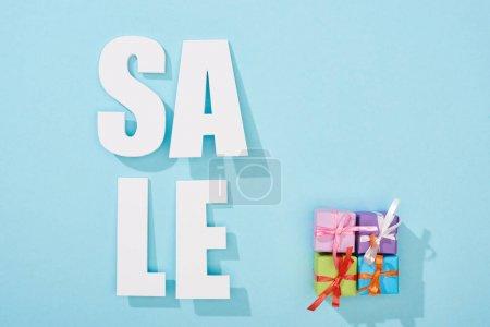 Photo pour Vue du dessus du lettrage blanc de vente près des boîtes-cadeaux festives sur fond bleu - image libre de droit