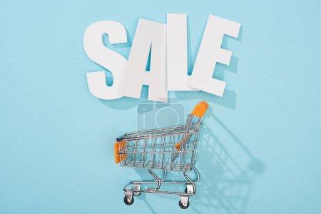 Photo pour Vue du dessus de blanc vente lettrage et panier vide sur fond bleu - image libre de droit