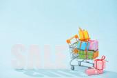 """Постер, картина, фотообои """"белые продажи надписей и праздничные подарочные коробки с луками в корзине на синем фоне"""""""