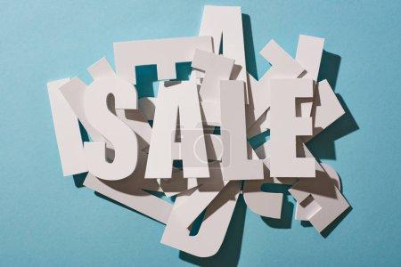 Photo pour Vue du dessus du lettrage blanc de vente sur pile de lettres sur fond bleu - image libre de droit