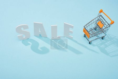 top view of white sale lettering near shopping trolley on blue background