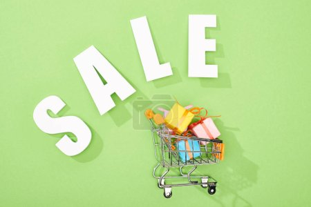 Photo pour Vue du dessus des boîtes-cadeaux décoratives dans le panier près de blanc vente lettrage sur fond vert - image libre de droit