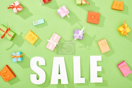 top view of scattered decorative gift boxes and shopping bags on green background with sale word
