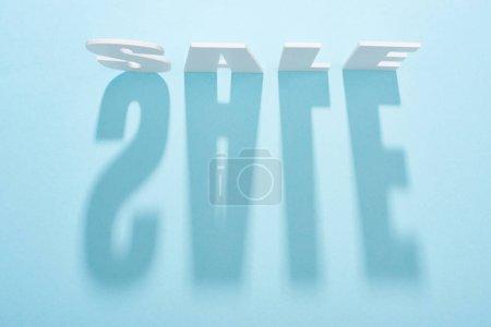 Photo pour Vue supérieure du lettrage blanc de vente avec l'ombre longue sur le fond bleu - image libre de droit