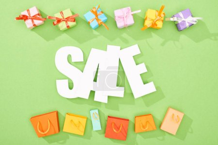 Photo for Top view of decorative gift boxes and shopping bags on green background with sale word - Royalty Free Image