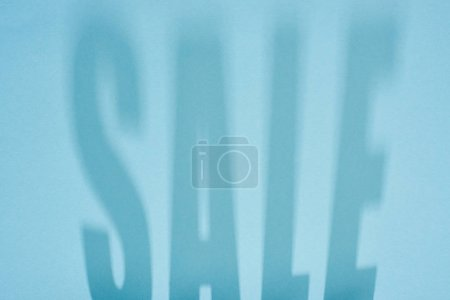Photo pour Ombre de vente lettrage sur fond bleu clair - image libre de droit