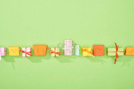 Photo pour Vue du dessus des boîtes-cadeaux décoratives et des sacs à provisions sur fond vert avec espace de copie - image libre de droit