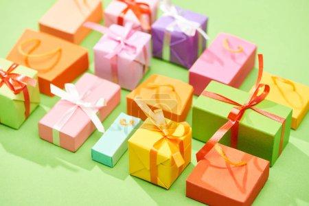 Photo pour Foyer sélectif de boîtes-cadeaux colorées décoratives sur fond vert - image libre de droit