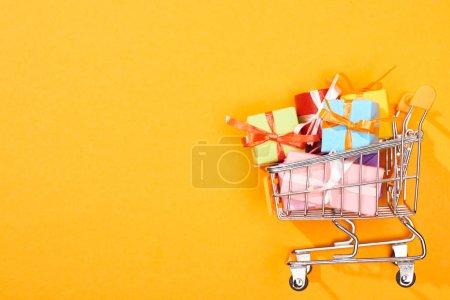 Photo pour Vue du haut du panier avec des cadeaux sur fond orange vif - image libre de droit