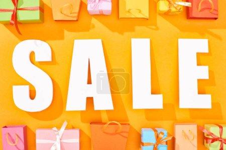 Photo pour Vue supérieure du lettrage blanc de vente près des sacs à provisions et présente sur le fond orange lumineux - image libre de droit
