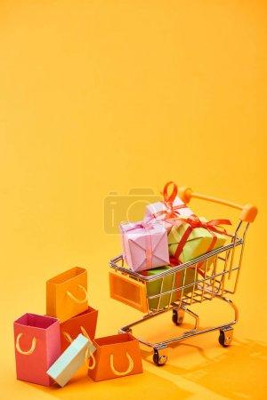 Photo pour Chariot d'achat avec des cadeaux près des sacs à provisions sur le fond orange lumineux - image libre de droit