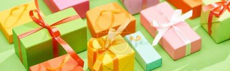 Photo pour Foyer sélectif des boîtes de cadeau colorées décoratives sur le fond vert, projectile panoramique - image libre de droit