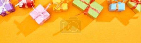 Foto de Vista superior de regalos festivos envueltos en fondo naranja brillante, tiro panorámico - Imagen libre de derechos