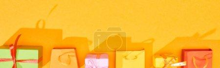 Photo pour Vue du dessus des cadeaux emballés de fête et des sacs à provisions sur fond orange vif, panoramique - image libre de droit