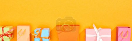 Photo pour Plan panoramique de sacs à provisions et cadeaux emballés festifs sur fond orange vif - image libre de droit
