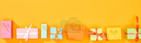 Photo pour Coup panoramique des sacs à provisions et des cadeaux enveloppés sur le fond orange lumineux - image libre de droit