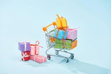 Photo pour Cadeaux emballés festifs dans le panier sur fond bleu - image libre de droit
