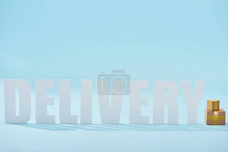white delivery word near closed cardboard boxes on blue background with copy space