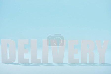 Photo pour Texte de livraison blanc avec des ombres sur fond bleu - image libre de droit