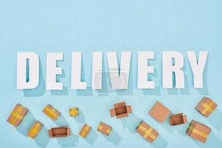 Photo pour Vue du dessus de la livraison de mots blancs près des boîtes en carton ouvertes et fermées sur fond bleu - image libre de droit