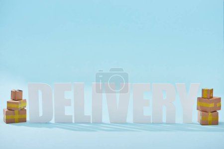 Photo for White delivery lettering with shadows near closed cardboard boxes on blue background - Royalty Free Image