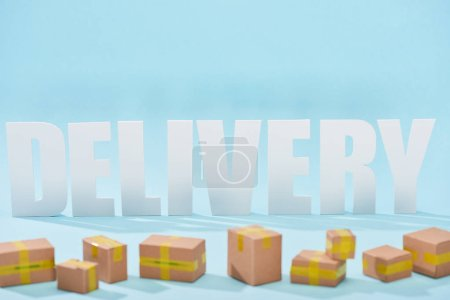 Photo for White delivery lettering with shadows behind closed cardboard boxes on blue background - Royalty Free Image