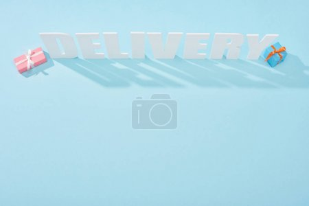 Photo for Top view of white delivery inscription with shadows near gift boxes on blue background - Royalty Free Image