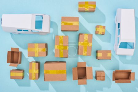 Photo for Top view of cardboard boxes and white vans on blue background - Royalty Free Image