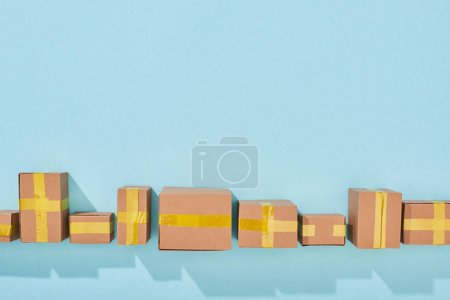 Photo for Top view of closed cardboard boxes with shadow on blue background - Royalty Free Image